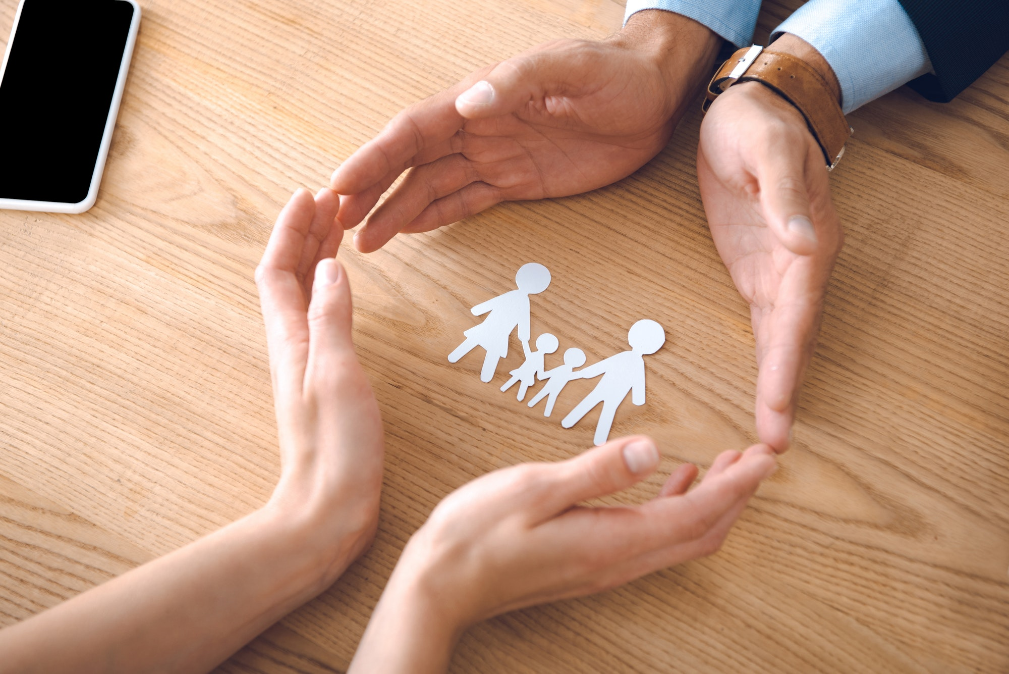 partial view of insurance agents and female hands with family paper model on wooden tabletop, family